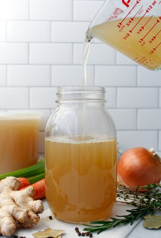 Pouring homemade chicken stock into a mason jar surrounded by ginger, carrots, an onion, rosemary, thyme, and peppercorns