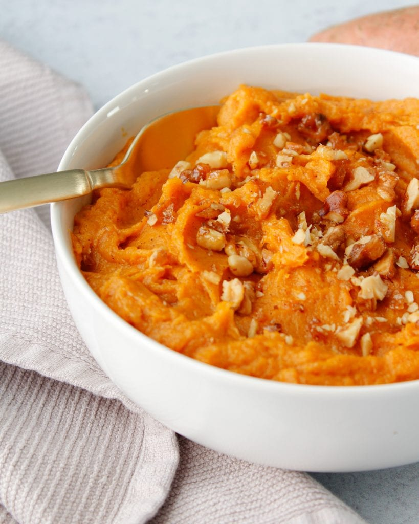 Honey Brown-Butter Mashed Sweet Potatoes in a white bowl topped with candied walnuts in a white bowl with gold cutlery.