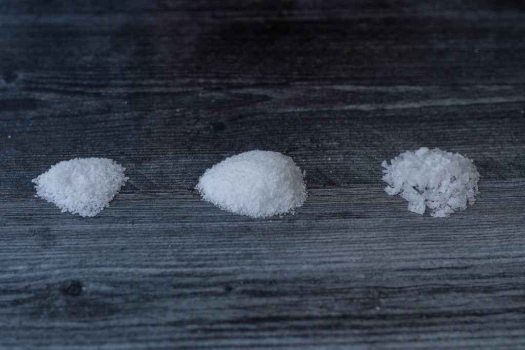 Piles of Morton Coarse Kosher Salt, Diamond Crystal Kosher Salt, and Maldon Sea Salt.