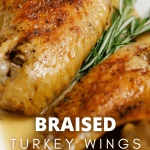 Braised Turkey Wings with Pan Gravy on a plate garnished with fresh rosemary