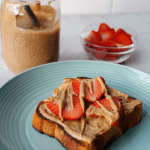 Toasted brioche bread topped with homemade almond butter and fresh cut strawberries on a teal plate. Bowl of strawberries and a mason jar filled with homemade almond butter in the background.
