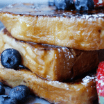 Close up of French Toast topped with blueberries and strawberries, drizzled with syrup and dusted with powdered sugar, on a grey plate.