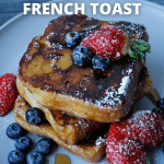 French Toast topped with blueberries and strawberries, drizzled with syrup and dusted with powdered sugar, on a grey plate.