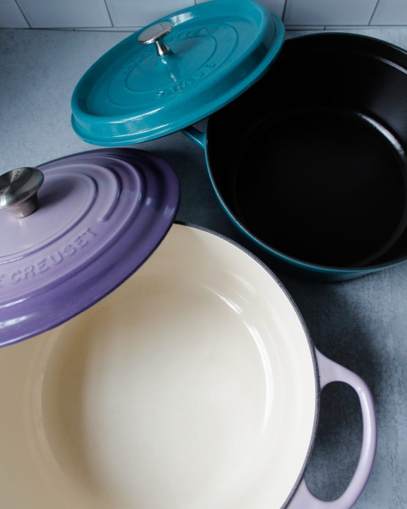5.5 Qt Le Creuset Dutch Oven in the color Provence and a 4 Qt Staub Cocotte, in the color Turquoise, with the lids open. Kitchen essentials.