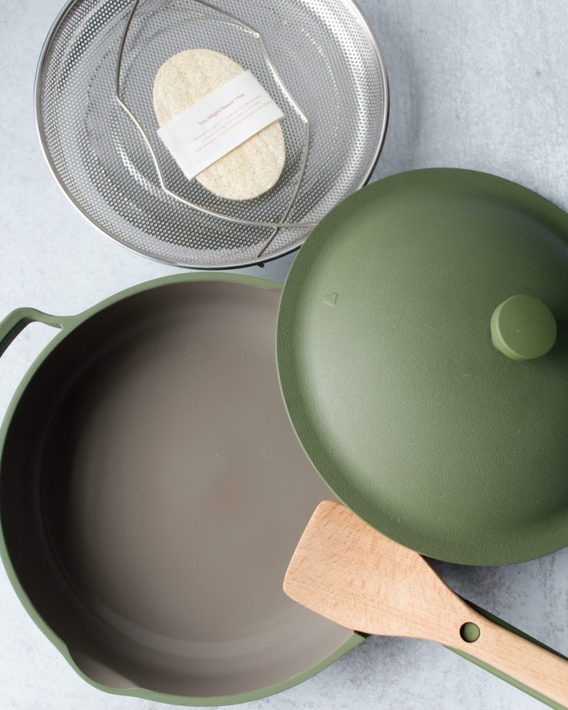 Always Pan by Our Place in the color Sage with a steamer basket, & a wooden spatula. Kitchen essentials.